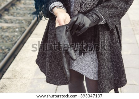 close-up of stylish woman at train station putting on her gloves - stock photo
