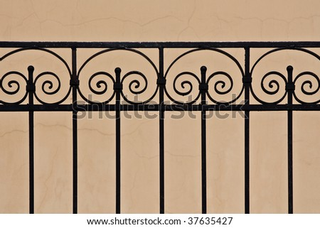 Close-up of stylish wrought-iron fence in the sunlight - stock photo
