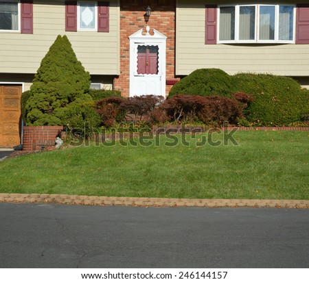 Close up of Suburban High Ranch brick landscaped home with cobble stone curb sunny autumn day residential neighborhood USA - stock photo