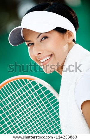 Close up of successful tennis player with towel on her shoulders - stock photo