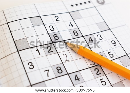 close up of sudoku game and yellow pencil. focus on a pencil - stock photo