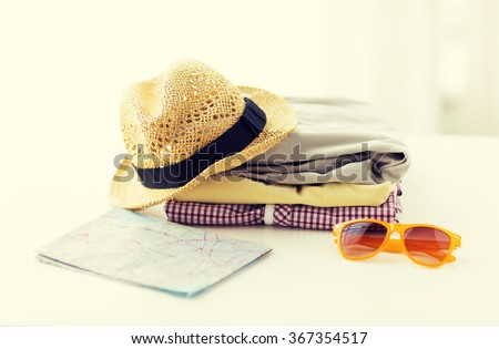 close up of summer clothes and travel map on table - stock photo