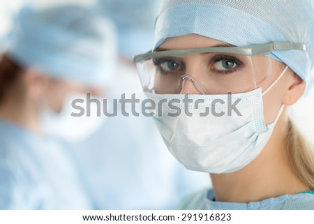 Close-up of surgeon woman looking at camera with colleagues performing in background in operation room - stock photo