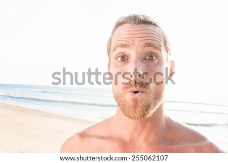 close up of surprised handsome man at the beach, looking at the camera. - stock photo