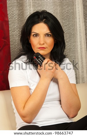 Close up of surprised woman holding remote control and sitting on sofa in living room - stock photo