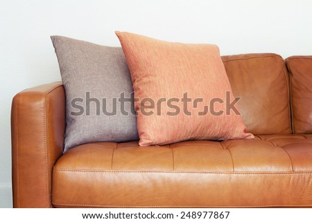 Close up of tan leather sofa with two linen cushions - stock photo