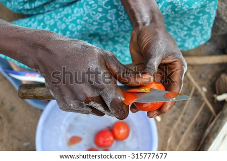 Close-up of Tanzanian woman cutting tomatoes for traditional meal in a rural village on Ukerewe Island, Lake Victoria, Tanzania - stock photo