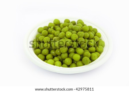 Close up of tasteful green peas ready for cooking on a white plate - stock photo