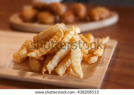 Close up of Tasty french fries on cutting board, on wooden table background - stock photo