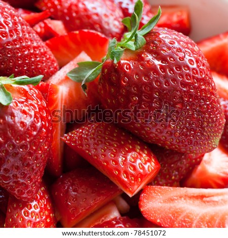 Close up of tasty fresh strawberries, cut into pieces and ready to eat - stock photo