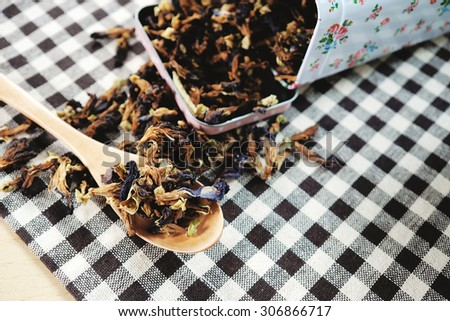 Close up of tea leaves made from Butterfly pea flower on tablecloth and wooden background. Shallow depth of field. - stock photo