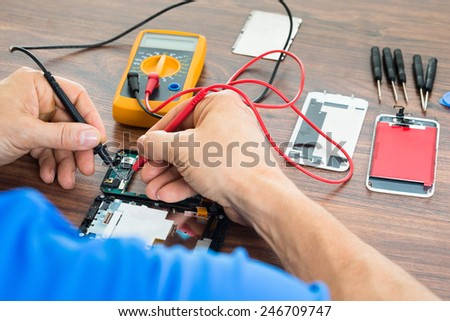 Close-up Of Technician Repairing Cellphone With Multimeter On Desk - stock photo