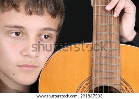 Close up of teen boy with his guitar - stock photo