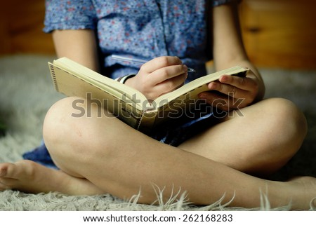 close up of teen girl writing into her notebook - stock photo