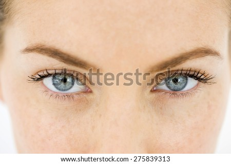 Close up of the blue eyes of a young woman. - stock photo