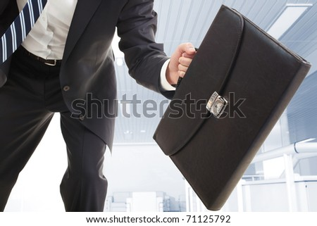 Close-up of the briefcase held by running businessman - stock photo