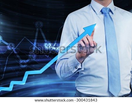 Close-up of the businessman who points out the growing arrow, which symbolises the concept of the success. A graph with drawn arrow signs 'buy' or 'sell' on the background. - stock photo