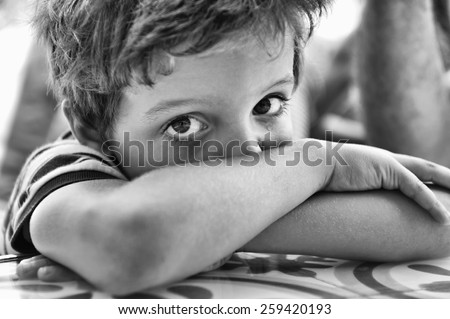 Close-up of the face of a child, with the crossed arms, crying and looking at the camera - stock photo