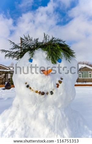 Close up of the face of a smiling snow man with a blue sky snowman - stock photo