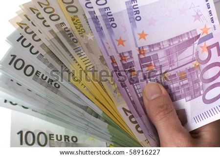 Close-up of the fan of 100, 200 and 500 Euro banknotes in hand on a white background. - stock photo
