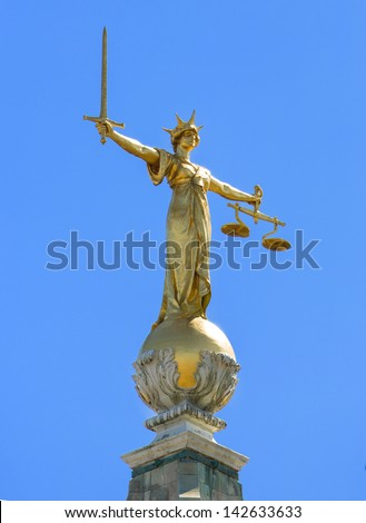 Close up of the golden statue on top of the Old Bailey the Central Criminal Court of England and Wales, a court in London and one of a number of buildings housing the Crown Court - stock photo
