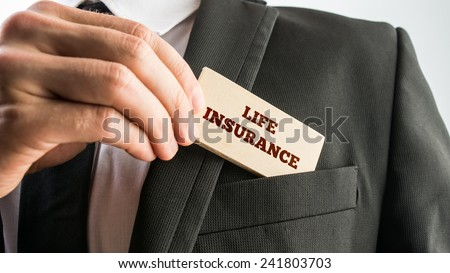 Close up of the hand of a businessman displaying a card reading - Life insurance - as he removes it from the pocket of his jacket in a conceptual image. - stock photo