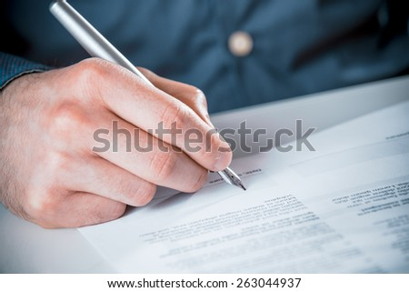 Close up of the hand of a man signing a business contract or document with printed text using a fountain pen - stock photo
