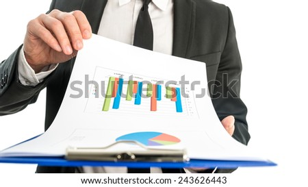Close up of the hands of a businessman analysing a set of graphs and holding a map with statistics in his hand. - stock photo