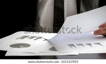 Close up of the hands of a businessman seated at his desk analysing a set of statistic report and holding a spreadsheet with graphs in his hand. - stock photo