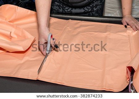 close-up of the hands of a seamstress with scissors in her office - copy space - stock photo