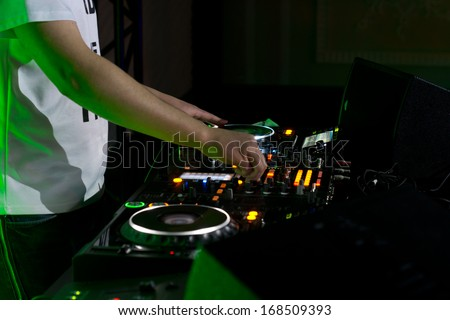 Close up of the hands of a young male disc jockey mixing and blending music tracks on his deck in the darkness of a party or nightclub - stock photo