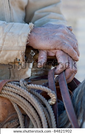 Close up of the hands of an old cowboy on his horse holding onto a saddle. - stock photo