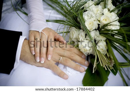 close up of the hands of bride and groom and wedding bouquet - stock photo