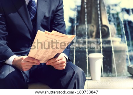 Close up of the hands of the businessman with a newspaper and coffee near the fountain. Outdoors - stock photo
