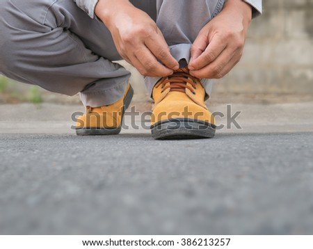 Close up of The man siting to wears safety shoes on street - stock photo