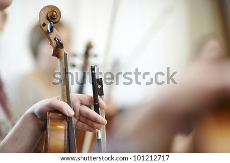 Close-up of the neck of a violin with a bow - stock photo