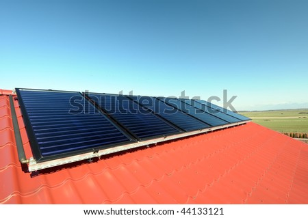 Close up of the new solar panels on red roof. - stock photo
