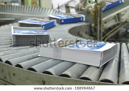 Close-up of the offset conveying process of a full-automatic perfect bound stitching unit. - stock photo