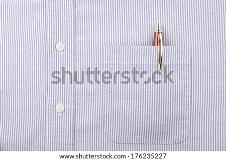 Close Up of the Pocket with Red and Gold Pen and Buttons on a Men's Blue Striped Shirt  - stock photo
