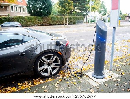 Close up of the power supply plugged into an electric car being charged. - stock photo