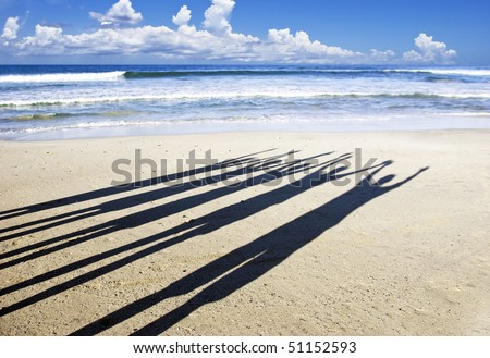 Close up of the shadows of five people with their arms in the air on the beach in late afternoon sun - stock photo
