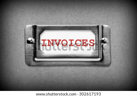 Close up of the word Invoices in red text on a drawer label holder from a filing cabinet. Processed in black and white for effect - stock photo
