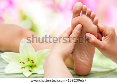 Close up of therapist's hands massaging female foot. - stock photo