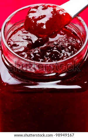 Close up of thick sweet strawberry jam  preserve on a spoon. With glass jar on red background. - stock photo