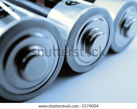 close-up of three aa-sized batteries in duotone blue - stock photo