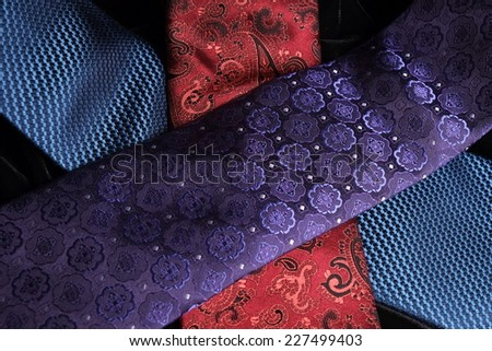 Close up of three (blue, purple and red) ties crossing on top of the other, while on display on black velvet - stock photo