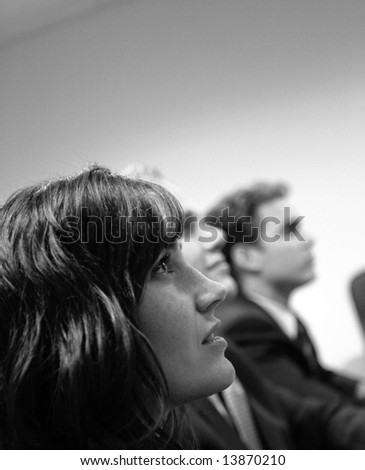 close up of three businesspeople sitting and looking in same direction - stock photo