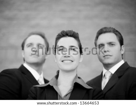 close up of three businesspeople standing together and smiling - stock photo