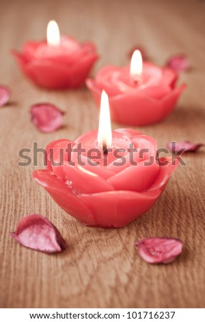 Close-up of three candles and flower petals - stock photo