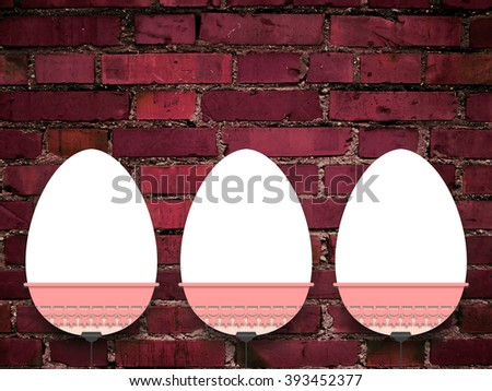 Close-up of three hanged blank Easter egg frames with clips against weathered red brick wall background - stock photo